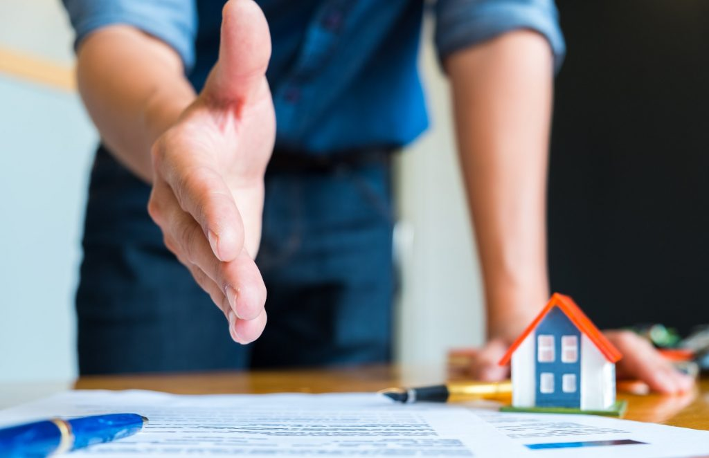 Home salesman stretches to shakes hands,Pen and model house on house plan.